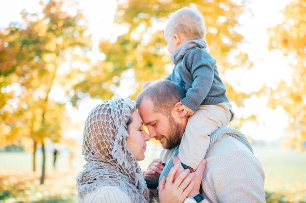 Baciare delle coppie della famiglia all'aperto con il loro fare da baby-sitter sulle spalle dei padri
