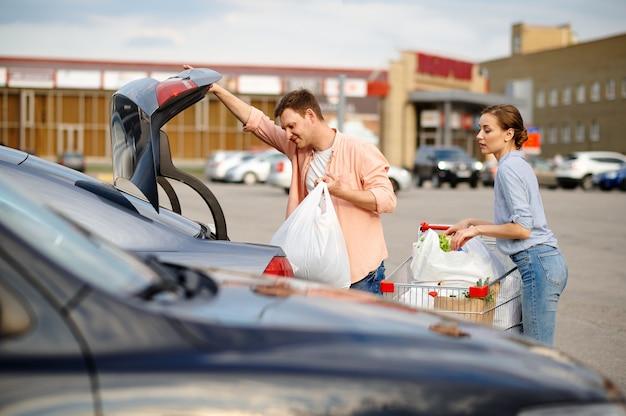La coppia di famiglia mette i loro acquisti nel bagagliaio