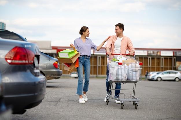Coppia di famiglia con borse nel carrello sul parcheggio dell'auto