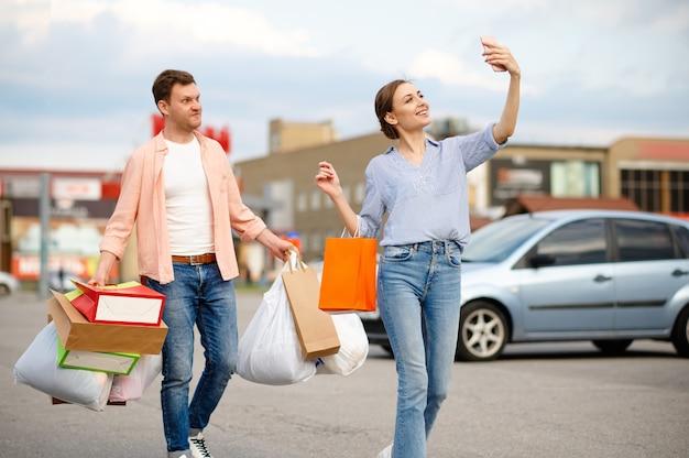 Coppia familiare con sacchetti di cartone fa selfie sul parcheggio del supermercato. clienti felici che trasportano acquisti dal centro commerciale, veicoli sullo sfondo