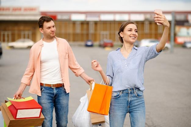 Coppia familiare con sacchetti di cartone fa selfie sul parcheggio del supermercato. clienti felici che trasportano acquisti dal centro commerciale, veicoli