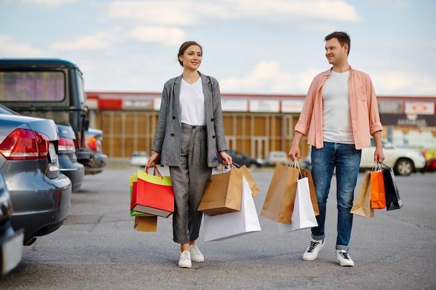 Coppia familiare con sacchetti di cartone sul parcheggio del supermercato. clienti felici che trasportano acquisti dal centro commerciale, veicoli