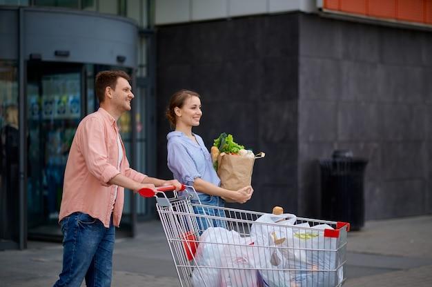 Coppia di famiglia con carrello sul parcheggio del mercato. clienti allegri che trasportano acquisti dal centro commerciale, uomo e donna al supermercato