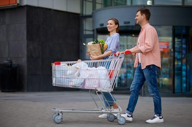 Coppia di famiglia con carrello sul parcheggio del mercato. clienti allegri che trasportano gli acquisti dal centro commerciale