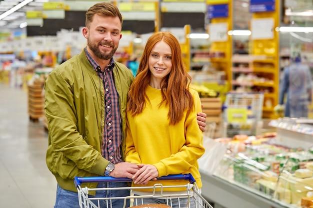 Coppia famiglia con camion in supermercato, abbracciando. nella navata