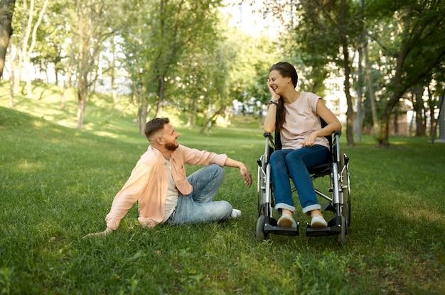 Coppia di famiglia con svaghi in sedia a rotelle nel parco