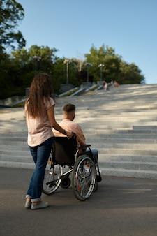 Coppia familiare con sedia a rotelle alle scale, handicap