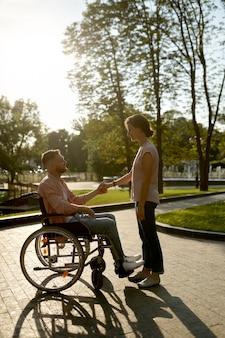 Coppia familiare con sedia a rotelle che cammina nel parco. paralitici e disabilità, cura di un disabile. marito e moglie superano le difficoltà insieme, relazioni affettuose