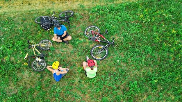 Famiglia in bicicletta in bicicletta all'aperto vista aerea dall'alto, i genitori attivi felici con il bambino si divertono e si rilassano sull'erba