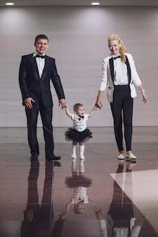 Famiglia, papà, mamma e figlia vestiti alla moda e alla moda belli e felici insieme
