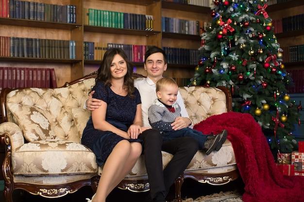 Famiglia. papà, mamma e figlioletto seduti sul divano vicino all'albero di natale.
