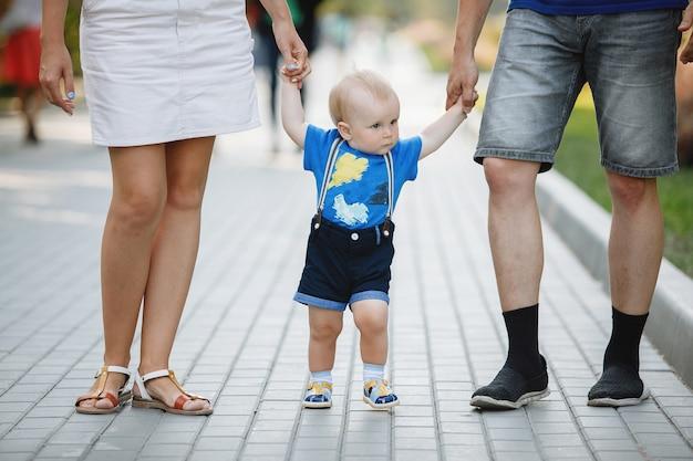 Papà di famiglia, mamma e figlio stanno camminando sul marciapiede nel parco cittadino in estate
