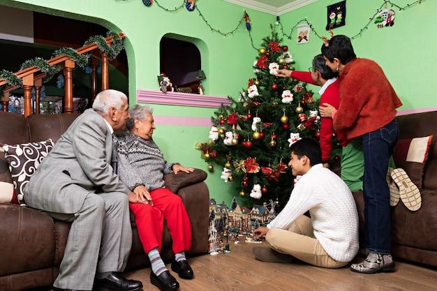 Una famiglia che decora insieme l'albero di natale a casa dei nonni