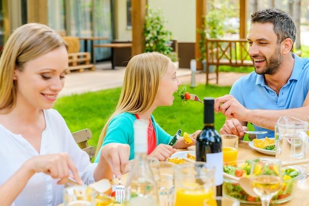 Cena di famiglia. felice giovane che dà da mangiare a sua figlia con insalata mentre si siede insieme al tavolo da pranzo