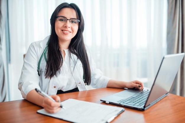 Concetto di medico di famiglia, specialista si siede al computer portatile