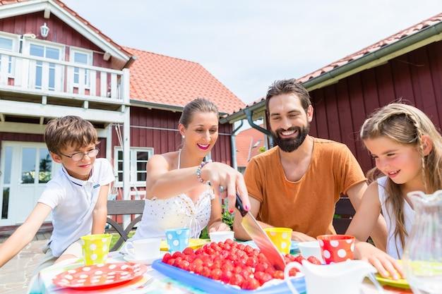 Famiglia che beve caffè e mangia torta davanti casa