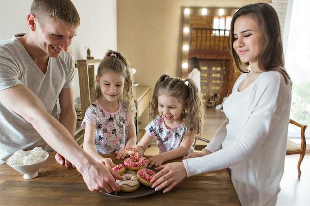 La famiglia mangia le torte la cena al panificio festa in cucina la macellazione del cibo