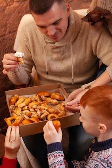 La famiglia mangia pasticcini, dolci in una scatola di cartone