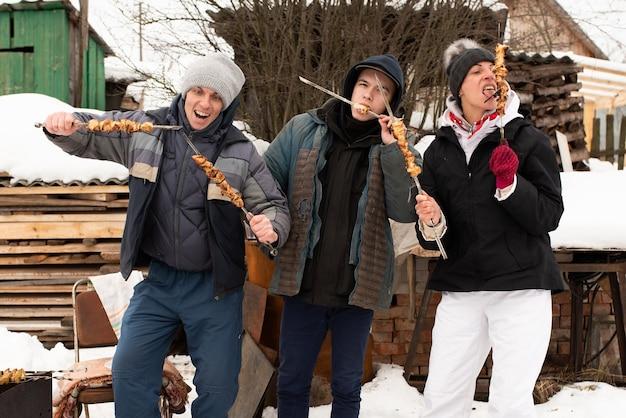 La famiglia mangia shashlik, in inverno per strada. per qualsiasi scopo.