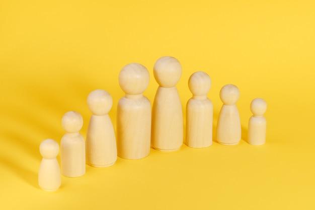 Famiglia di otto membri realizzati con figurine di legno su sfondo giallo