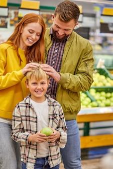 La famiglia si diverte a fare shopping con il bambino, i giovani genitori nel corridoio del supermercato con il ragazzo carino, in abbigliamento casual, si divertono