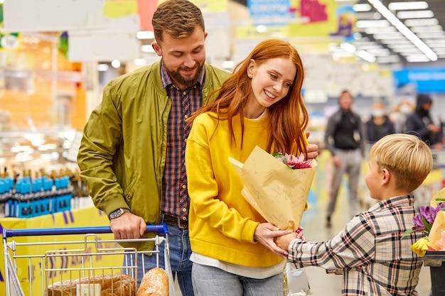La famiglia ama fare shopping con il bambino, i giovani genitori nella corsia del supermercato con il ragazzo carino, in abbigliamento casual, sorride