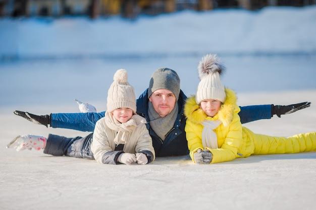 La famiglia gode dell'inverno sulla pista di pattinaggio all'aperto