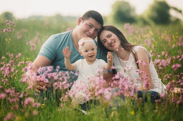 Famiglia che gode della vita insieme nel campo estivo con fiori selvatici.