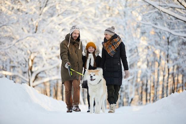 Famiglia che gode della passeggiata con il cane
