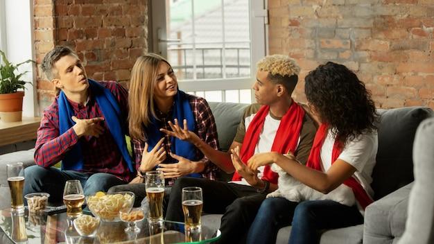 Famiglia. gente entusiasta che guarda la partita sportiva, il campionato a casa. gruppo multietnico di amici, tifosi che tifano per la squadra del cuore