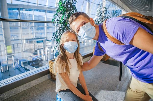 Famiglia in maschera facciale in aeroporto. padre e figlio indossano una maschera facciale durante il coronavirus e l'epidemia di influenza