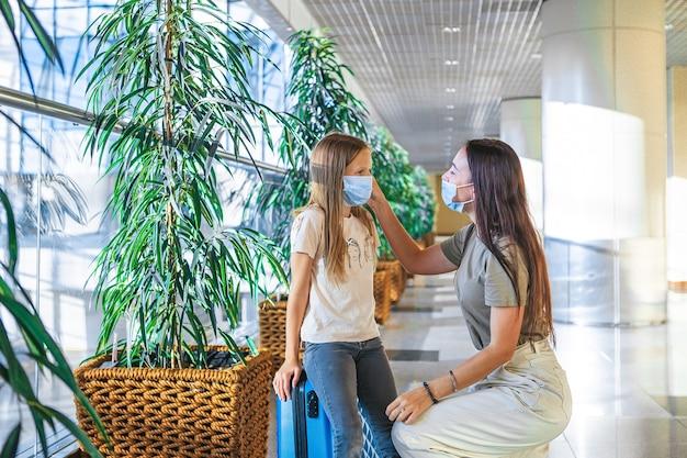 Famiglia in maschera facciale in aeroporto internazionale.