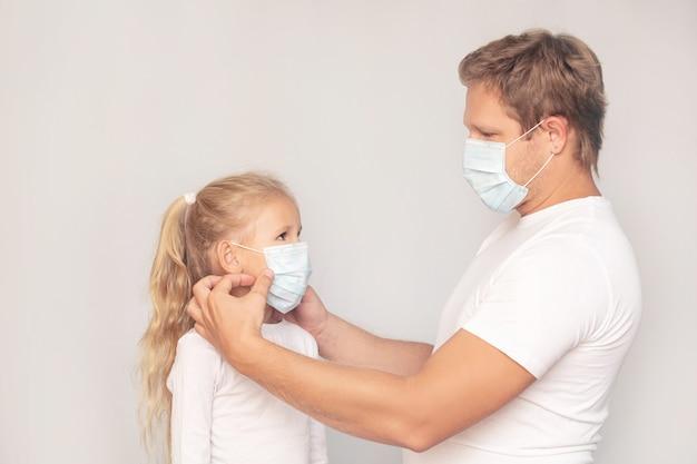 Padre di famiglia e figlia in maschere mediche insieme su uno sfondo isolato
