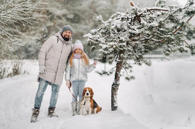 Padre e figlia di famiglia in una passeggiata con il loro cane nella foresta invernale.