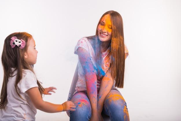 Famiglia, festival di holi e concetto di vacanze - bambina che gioca con sua madre ricoperta di vernice