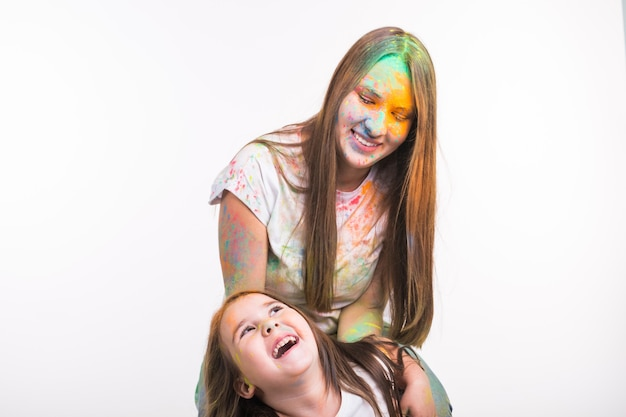Famiglia, festival di holi e concetto di vacanze - donna e bambina sorridente ricoperta di polvere colorata su superficie bianca