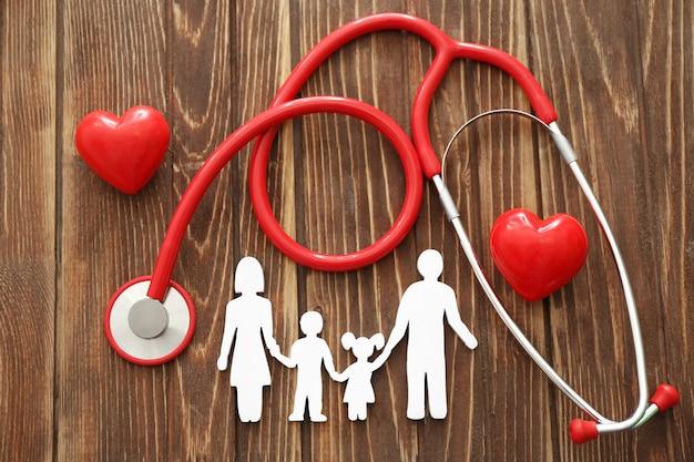 Figura di famiglia, cuori rossi e stetoscopio sul tavolo di legno. concetto di assistenza sanitaria