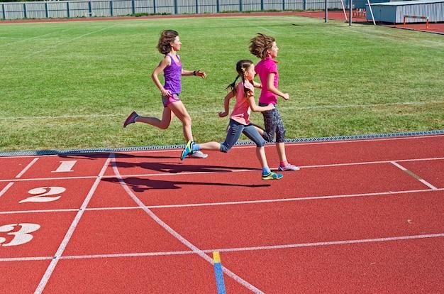 Famiglia fitness, madre e bambini che corrono sulla pista dello stadio, formazione e bambini sport concetto di stile di vita sano