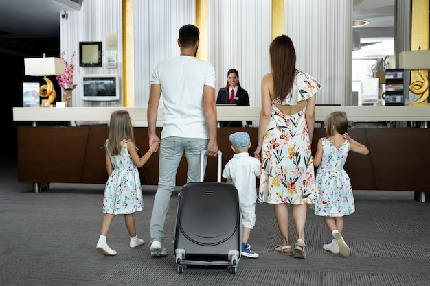 Una famiglia di cinque persone entra nella hall dell'hotel per fare il check-in alla reception per le vacanze.