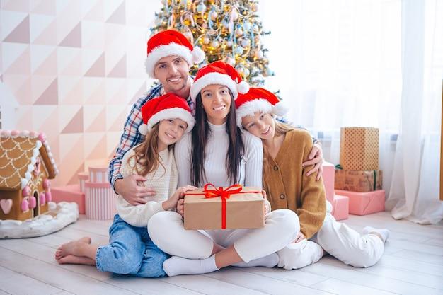 Famiglia di quattro persone durante le vacanze di natale a casa. buon natale e buone feste.