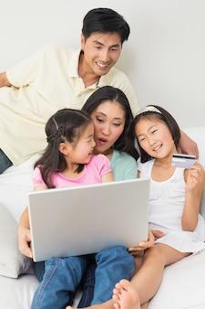 Famiglia di quattro persone che fanno shopping online