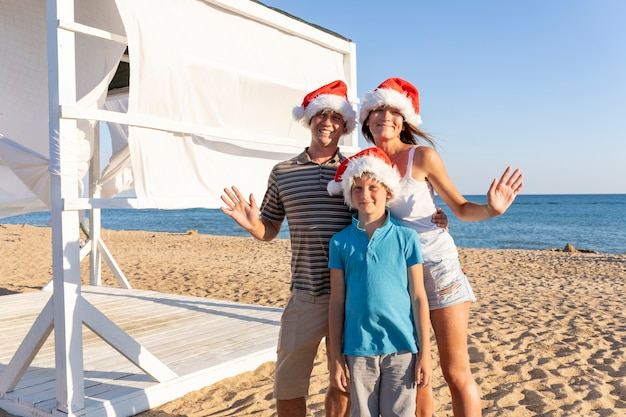 Una famiglia di quattro persone, mamma papà e due bambini in cappelli di babbo natale in spiaggia di sabbia del mare. famiglia felice di natale che celebra il nuovo anno in riva al mare.