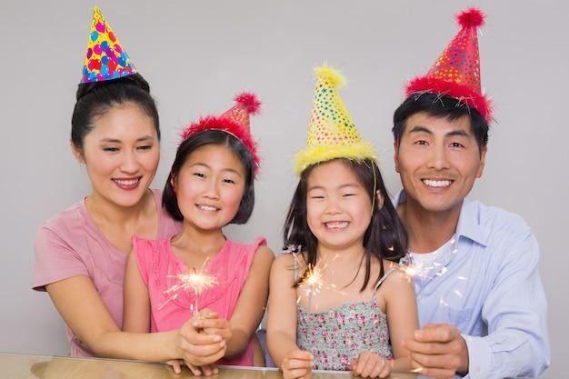 Famiglia di quattro persone che giocano con petardi a una festa di compleanno