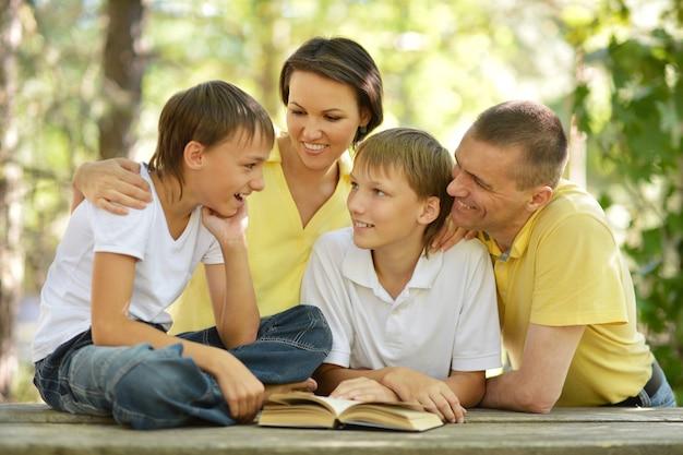 Famiglia di quattro persone che leggono all'aperto a tavola con un libro