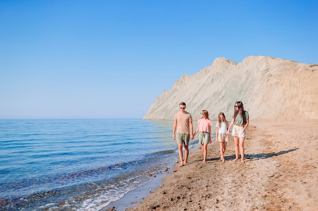 Famiglia di quattro persone a piedi lungo la spiaggia in vacanza estiva
