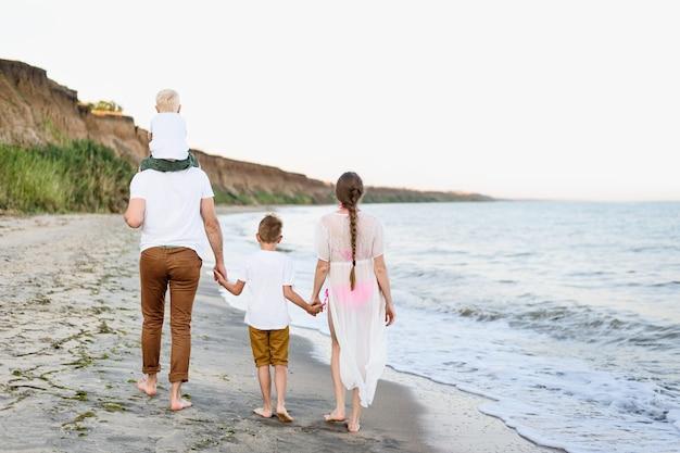 Famiglia di quattro persone che camminano lungo la riva del mare. genitori e due figli. vista posteriore