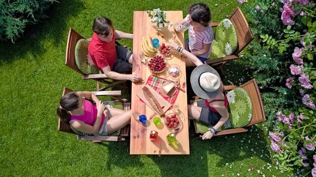 Famiglia ed amici che mangiano insieme all'aperto sul ricevimento all'aperto di estate. vista aerea del tavolo con cibo e bevande dall'alto. concetto di tempo libero, vacanze e picnic