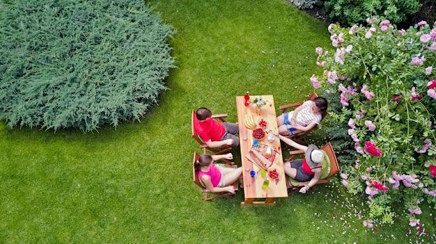 Famiglia e amici che mangiano insieme all'aperto sulla festa in giardino estivo. vista aerea del tavolo con cibi e bevande dall'alto. tempo libero, vacanze e concetto di picnic