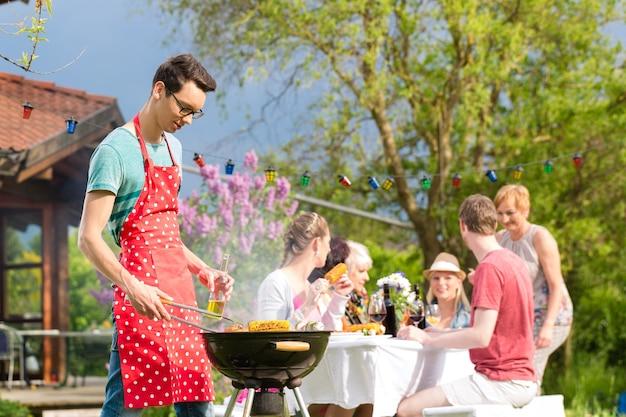 Famiglia e amici che mangiano barbecue alla festa in giardino, l'uomo in primo piano sulla griglia, sullo sfondo la gente beve e mangia