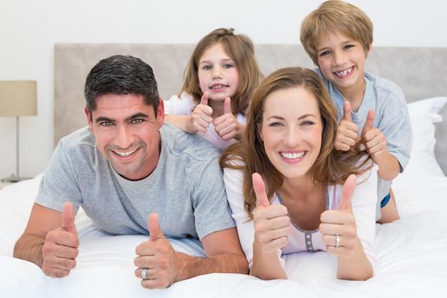 Famiglia che gesturing i pollici su a letto